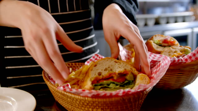 stockvideo's en b-roll-footage met chef-kok regelen van plantaardige sandwiches in de mand 4k 4k - sandwich