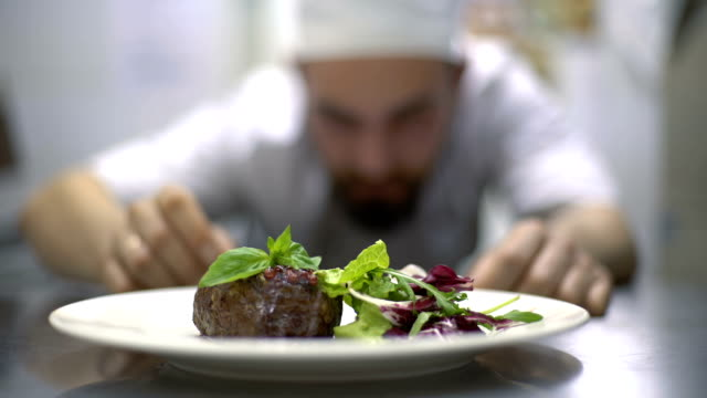Chef at commercial cuisine in a restaurant Chef is finishing meal teasty beef steak with salad for guest of restaurant. Final touch basil leaf garnish stock videos & royalty-free footage