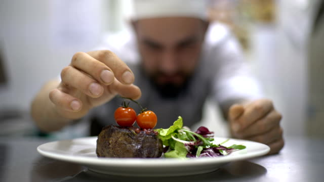 Chef at commercial cuisine in a restaurant Chef is finishing meal teasty beef steak with salad for guest of restaurant. Final touch tomatoes ingredient stock videos & royalty-free footage