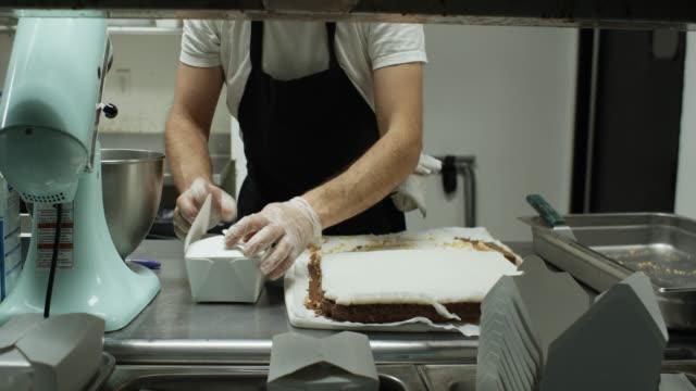 vídeos de stock, filmes e b-roll de chef boxing up sobremesas veganas para entrega durante o surto covid-19 - vegetarian meal