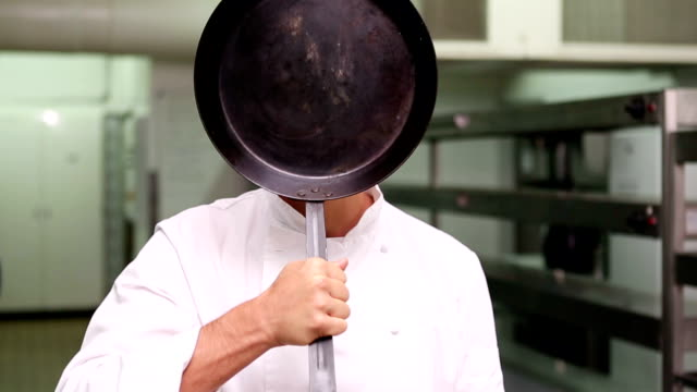 Chef changing face behind a frying pan video