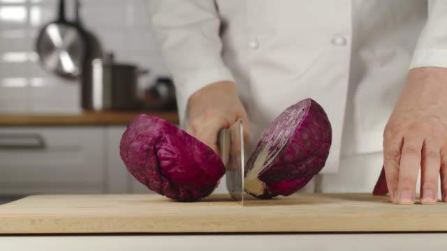 SLOW MOTION: Chef Chopping A Head Of Red Cabbage On Wooden Board While Cooking SLOW MOTION: Chef Chopping A Head Of Red Cabbage On Wooden Board While Cooking cabbage stock videos & royalty-free footage