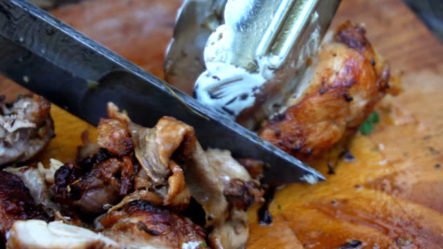 Chef chopping grilled chicken meat on cutting board. video