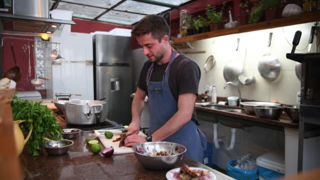 szef kuchni siekanie suszonych pomidorów w kuchni - kultura włoska filmów i materiałów b-roll