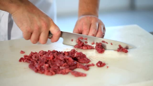chef cook hands cut the meat on chopping board in restaurant kitchen close up - meat stock videos and b-roll footage