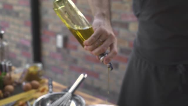 chef cook pouring olive oil from bottle while cooking salad at bricks background. male hand taking olive oil bottle while food preparation on kitchen cuisine. cooking healthy food concept - olio d'oliva video stock e b–roll