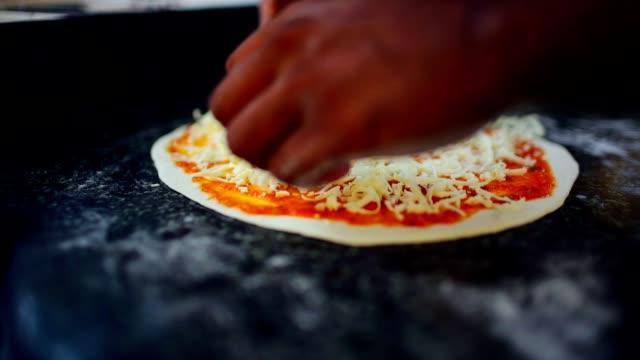 シェフのピザ屋でピザを準備中生地に粉チーズを入れて ビデオ