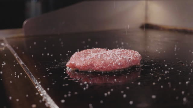 chef cooking and salting fresh meat cutlet for the burger, street food - burgers stock videos and b-roll footage