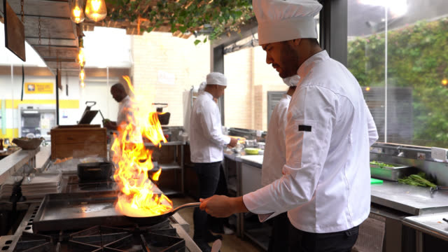 Chef cooking flambe in a pan looking focused