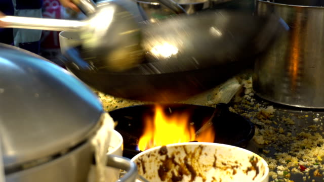 Chef cooking fried rice on fire during in a restaurant kitchen. Chef cooking fried rice on fire during in a restaurant kitchen. stir fried stock videos & royalty-free footage