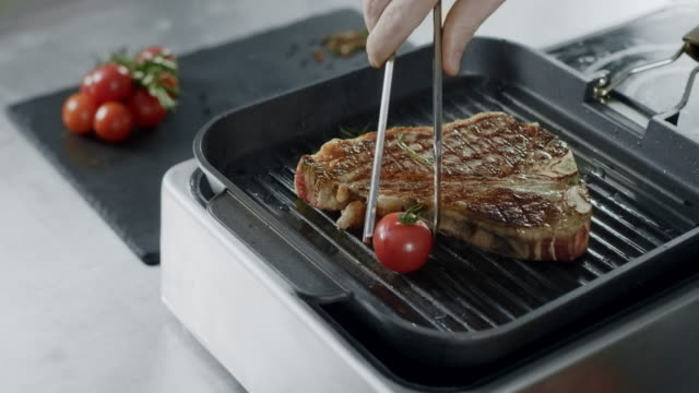 chef cooking grill steakn. closeup chef hands putting vegetables at frying fork - płyta do pieczenia filmów i materiałów b-roll