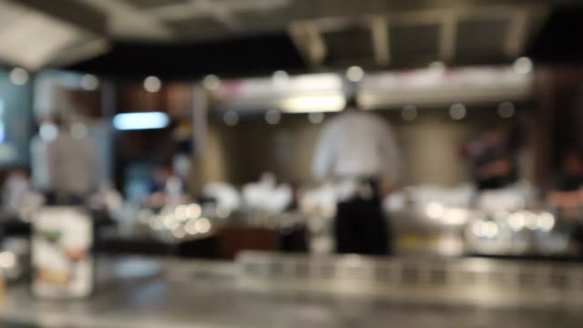 chef cooking in restaurant kitchen blurred defocused background - busy restaurant kitchen stock videos & royalty-free footage