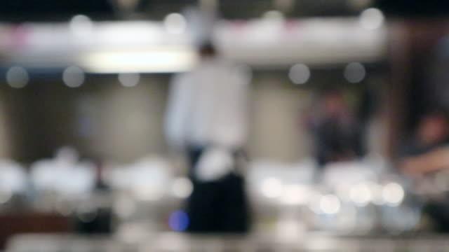 Chef cooking in restaurant kitchen blurred defocused background