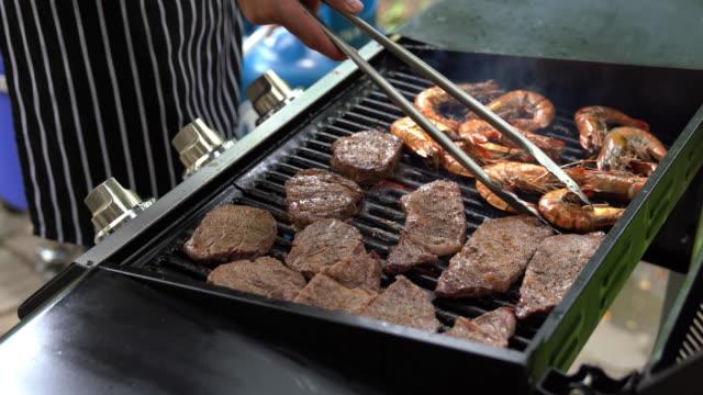 chef cooking of beef and prawn bbq steak - płyta do pieczenia filmów i materiałów b-roll