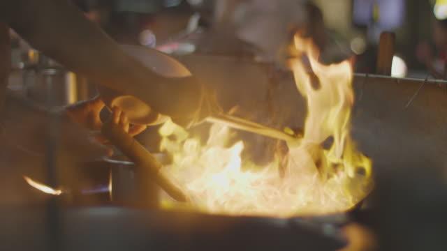 vídeos y material grabado en eventos de stock de chef cocina en sartén en el horno llameante en 4 k lenta - comida china