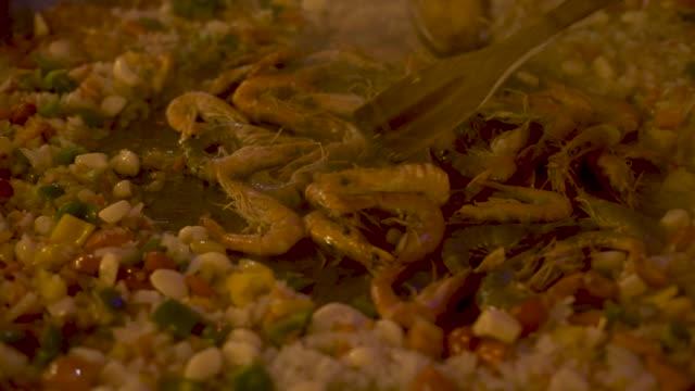 vídeos y material grabado en eventos de stock de chef cocina camarones en la sartén caliente para paella española de cerca. proceso de preparación de los alimentos en cocina de restaurante españa. cocina tradicional española. concepto de preparación de alimentos - comida española
