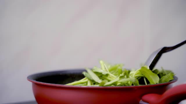 シェフクッキングホットパンでフライドウォーターほうれん草。 - ベジタリアン料理点の映像素材/bロール