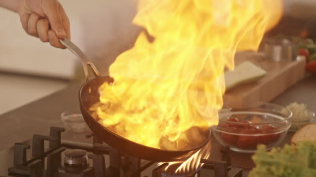 Chef cooking with fire, grilling vegetables Chef cooking with fire, grilling vegetables frying pan stock videos & royalty-free footage