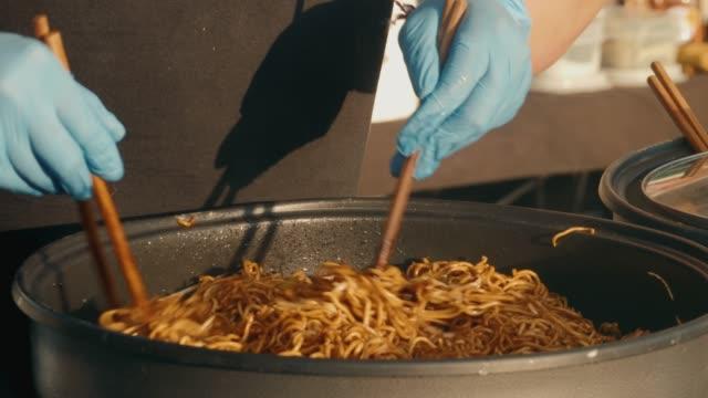 Chef cooking Yakisoba noodle on street food market. cooking Yakisoba Fried Japanese noodle with onion