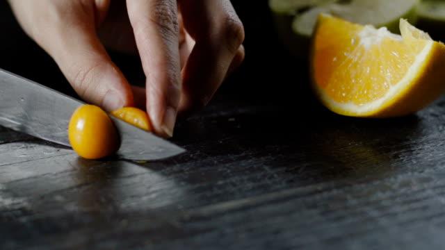 stockvideo's en b-roll-footage met chef-kok bezuinigingen cape gooseberry op donkere houten tafel - fresh start yellow