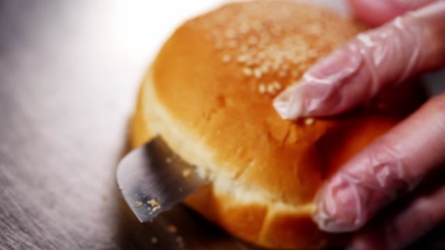 chef cuts hamburger soft bun on metal table slow motion