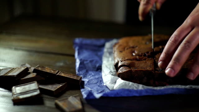 kocken skär choklad dessert på bordet. skivning chokladkaka. - brownie bildbanksvideor och videomaterial från bakom kulisserna