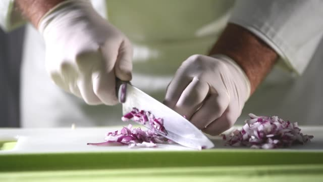 Chef cutting fresh red onion on a cutting board