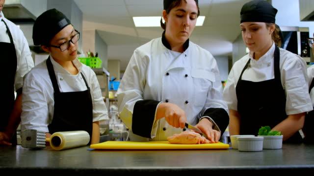 vídeos de stock e filmes b-roll de chef cutting meat on chopping board in kitchen 4k - avental
