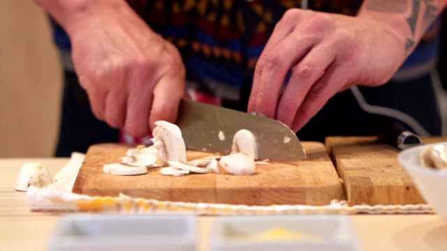シェフがまな板でキノコを切る ビデオ