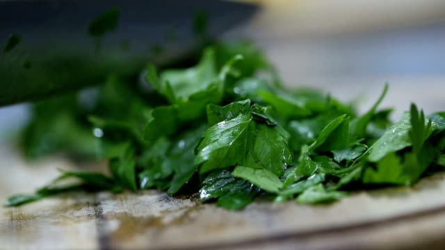 chef cutting parsley on a wooden board. close up video