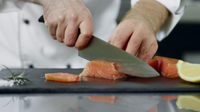 chef cutting salmon fillet at kitchen. closeup hands slicing fresh fish. - ryba filmów i materiałów b-roll