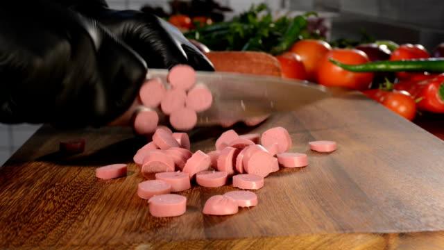 koch-schneiden-würstchen in der küche - wurst stock-videos und b-roll-filmmaterial