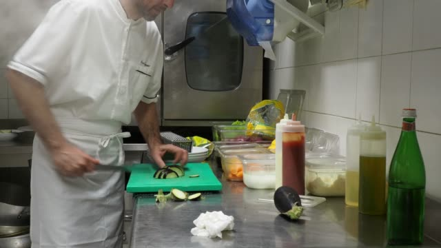 Chef cutting the aubergines in the restaurant's kitchen