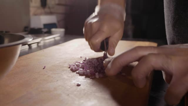 Chef cutting up an onion with a knife video