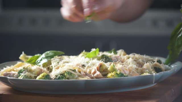 kocken dekorerar basilikablad med spaghettipasta på en tallrik i restaurangköket. livsmedelsingrediensen. matlagning på köket. tillagad för gourmet. laga mat att äta. gastronomi kulinariska. god middag. - basilika ört bildbanksvideor och videomaterial från bakom kulisserna