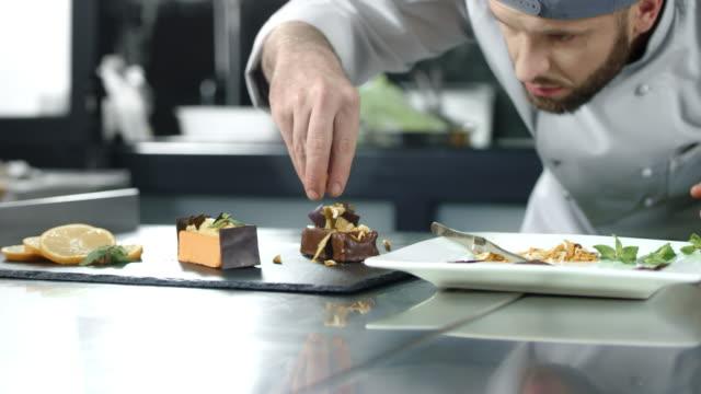 vídeos y material grabado en eventos de stock de chef decorar pastel en la cocina. chef de primer plano haciendo postre a cámara lenta. - comida gourmet