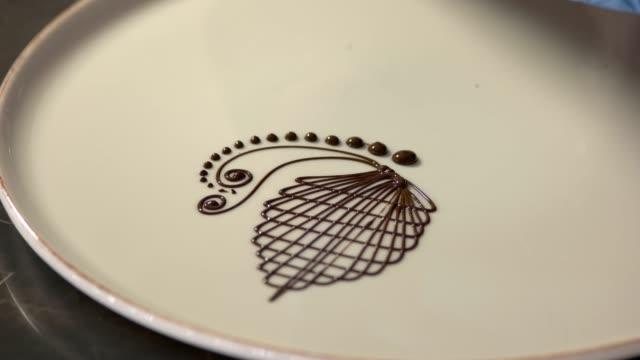 chef-dekorationsteller für schokoladendessert im restaurant. - zuckerguss stock-videos und b-roll-filmmaterial