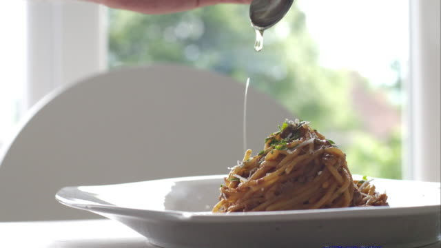 Chef dressing pasta with olive oil video