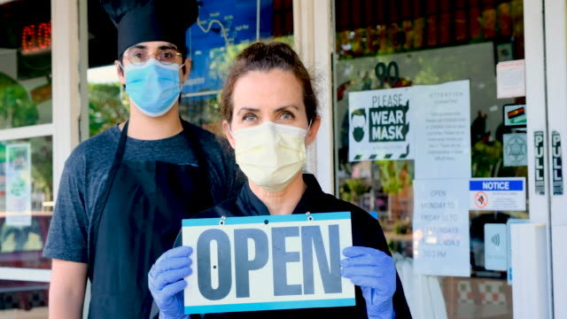vídeos de stock e filmes b-roll de chef fast food restaurant and mature female owner posing wearing a mask holding an open sign - covid restaurant