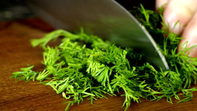 chef finely chop fresh juicy dill with kitchen knife on wooden cutting board. - articoli casalinghi video stock e b–roll