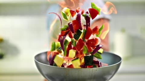 stockvideo's en b-roll-footage met slo mo chef-kok flambaying groenten - 4k resolutie