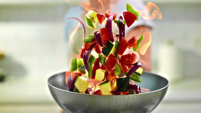 SLO MO chef flambaying vegetables Slow motion panning medium shot of a chef flambaying the colorful vegetables over the stove. commercial kitchen stock videos & royalty-free footage