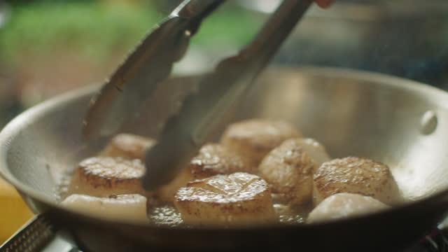 vídeos de stock, filmes e b-roll de slo mo chef vira vieiras meio cozidas em uma frigideira - frutos do mar