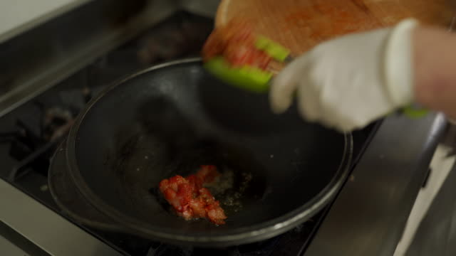 Chef frying chicken meat in wok at commercial kitchen