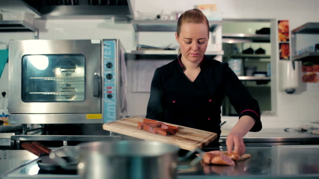 Chef frying frankfurters on the stove video