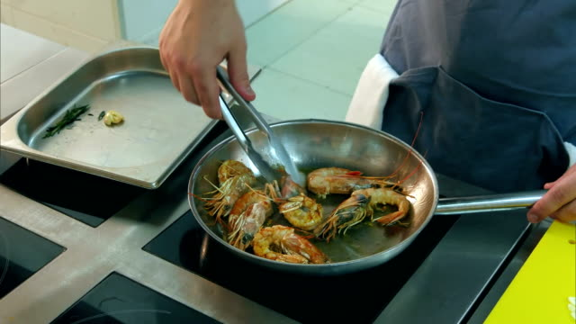 Chef frying royal shrimps on a pan and adding sunflower oil video