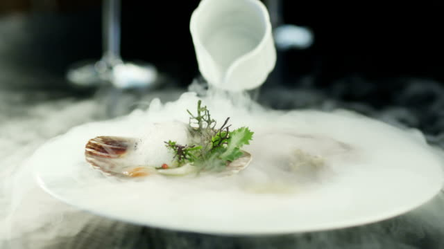 chef garnishing scallops with dry ice in luxury restaurant. - fine dining stock videos and b-roll footage