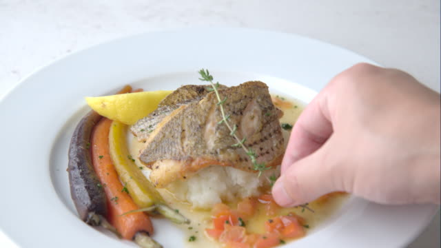 chef garnishing seabass poele flat - морской окунь стоковые видео и кадры b-roll