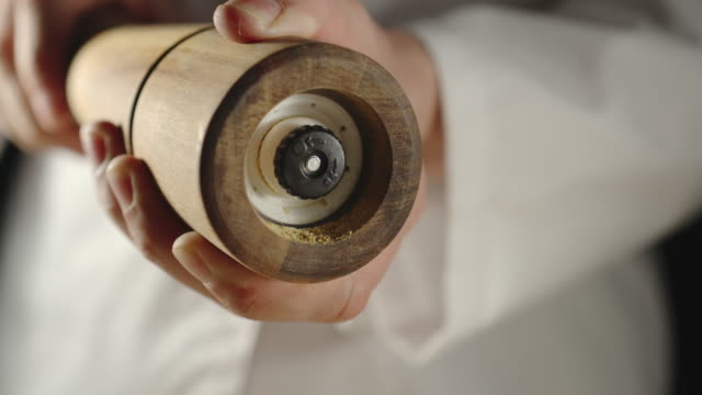 slow motion: chef grinding spice in a wooden grinder while cooking - grindare video stock e b–roll