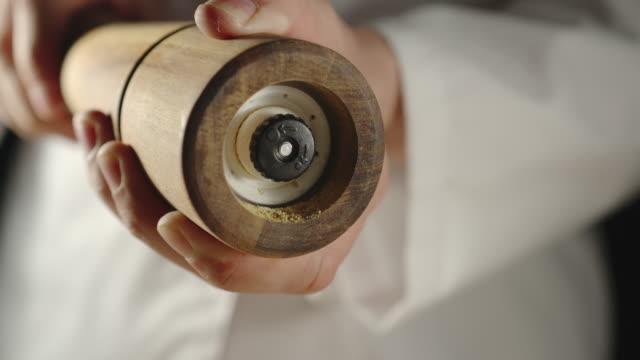 slow motion: chef mahlen gewürz in einer holzmühle beim kochen - grind stock-videos und b-roll-filmmaterial